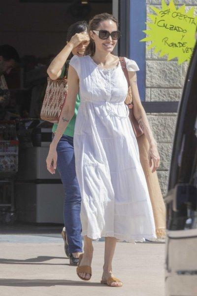 Счастливая Анджелина Джоли в белом  платье, гуляет с детьми по магазинам